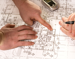engineers pointing to blueprints